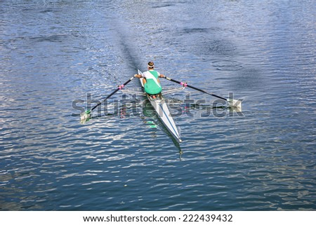 Women Rower in a boat, rowing on the tranquil lake - stock photo