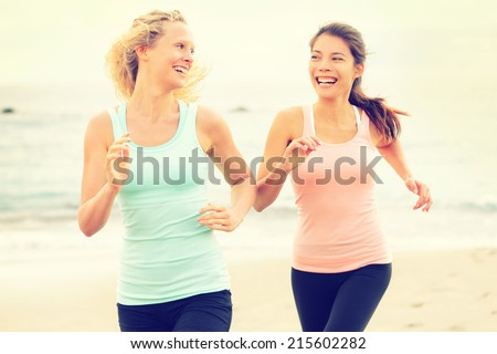 Women running exercising jogging happy on beach training as part of healthy lifestyle. Two fit female runners talking happy and smiling during workout. Multiracial Asian and Caucasian woman. - stock photo