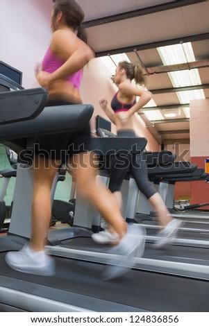 Women running fast on treadmill at gym - stock photo