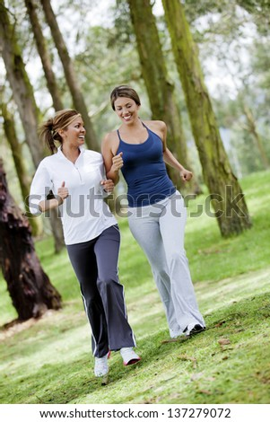 Women running outdoors in the woods looking very happy - stock photo