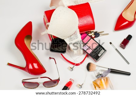 Women's accessories. Open ladies handbag with scattered accessories. Stylish red shoes with heels. - stock photo