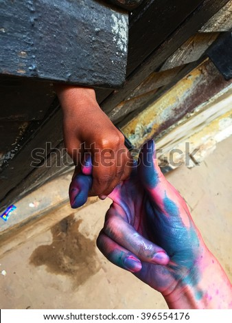 Women's and child's hands, woman and child holding hands, indian child holding hand, Holi scene in Varanasi, painted hand, friendship hands, jointed hands of a kid and a girl, Holi festival, India - stock photo
