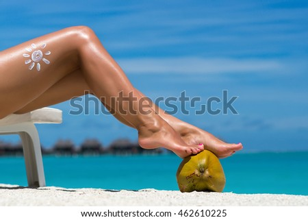 Women's beautiful legs on coconut on the beach, blue sea background