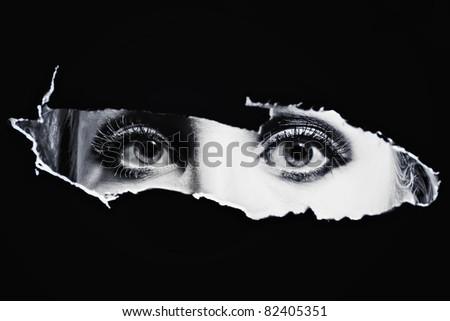 Women's bl eyes spying through a hole - stock photo