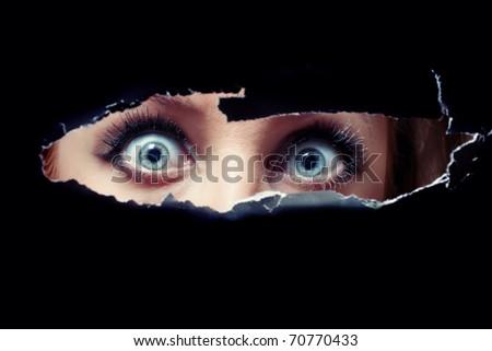 Women's blue eyes spying through a hole - stock photo