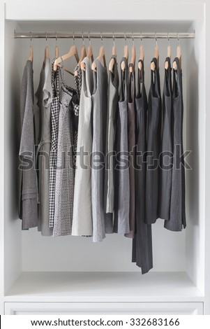 women's dress  and clothes hanging in white wardrobe - stock photo