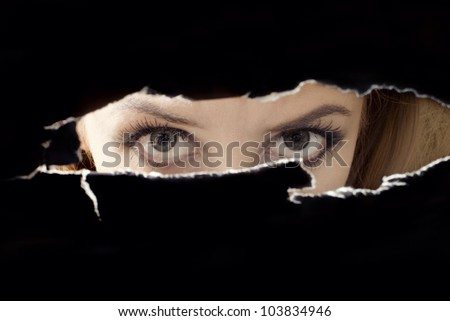 Women's eyes spying through a hole close up - stock photo