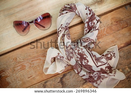 Women's fashion accessories. Sunglasses and a floral scarf  - stock photo