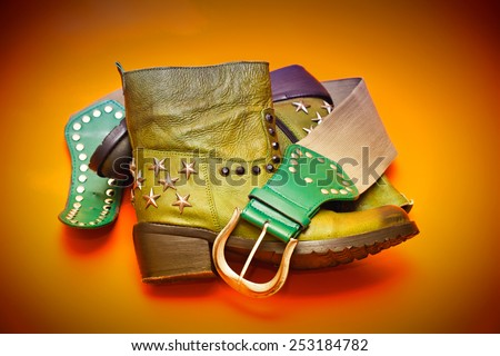women's fashion cowboy outfit: green leather boots rivets, green leather belt with buckle - stock photo