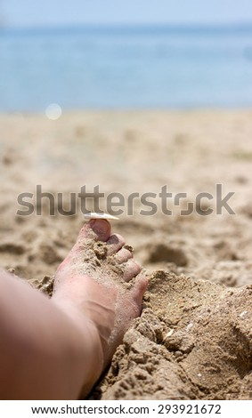 Women's foot close-up in the sand at the beach - stock photo