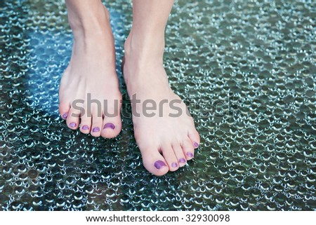 Women's foot on bubbled glass. - stock photo