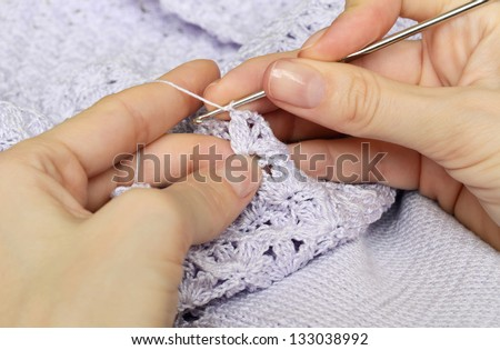 Women's hands crocheting lilac baby dress