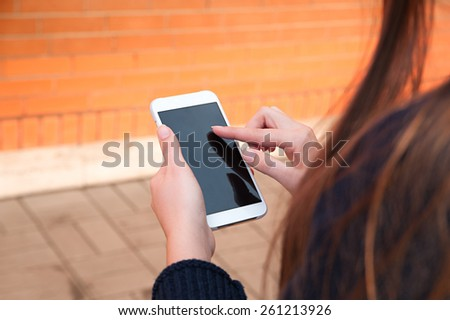 Women's hands holding the phone - stock photo