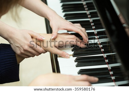 Women's hands on the keyboard of piano. girl plays. music teacher - stock photo