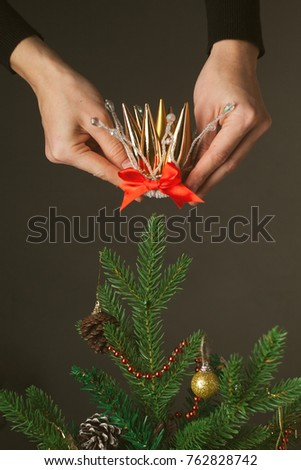 women's hands wear a crown on a Christmas tree - the concept of a holiday, on the eve of a birth, preparation for celebrations