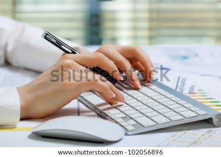 Women's hands with a pen and keyboard - stock photo