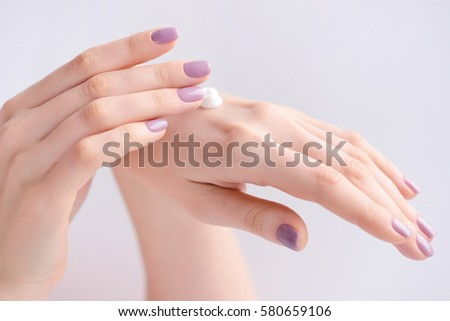 Women's hands with pink manicure applying cream. The concept of skin care.