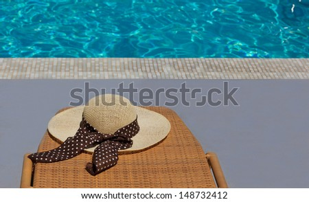 Women's hat on chair at the pool