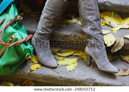 women's high-heeled boots and a bag outdoors  - stock photo