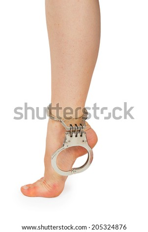 Women's leg in handcuffs isolated on white background - stock photo