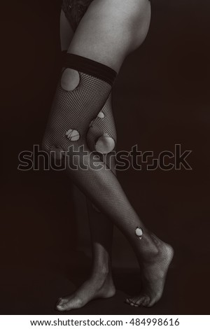 Women's legs dressed in ripped stockings on a black background