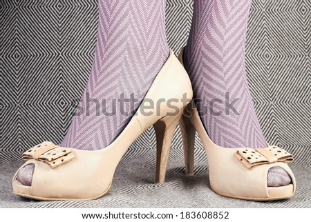 women's legs in delicate tights  with beige leather  peep-toe shoes - stock photo