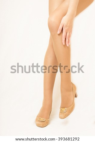 Women's legs in pantyhose and shoes. Neutral color - stock photo