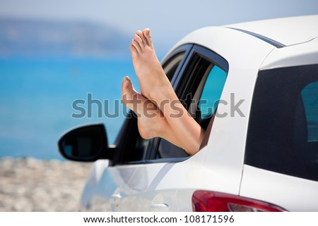 Women's legs sticking out the car window . The concept of relaxation and travel - stock photo