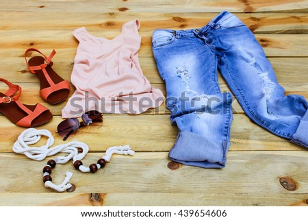Women's summer clothing and accessories: tank top, jeans, sunglasses, belt, shoes on wooden background.