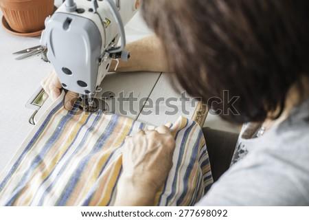 Women sew on sewing machine. White machine - stock photo