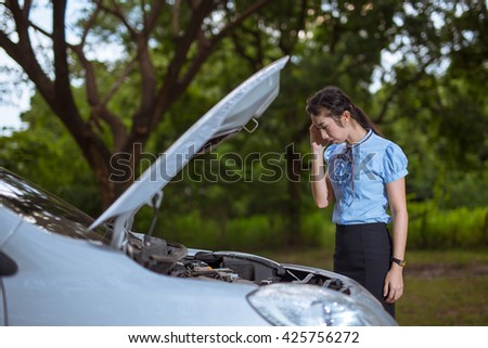 Women She opened the hood Broken car on the side See engines that are damaged or not. Women Broken car in Forest - stock photo