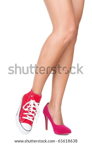 Women shoes. Red high heels and sports shoes / sneakers. Closeup of woman legs and feet wearing two different shoes. Isolated on white background.