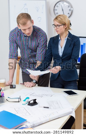 Women showing business plan to her coworker at office - stock photo