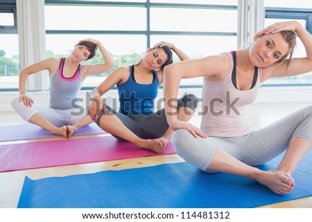 Women sitting and stretching at yoga class in fitness studio - stock photo