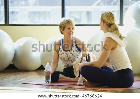 Women sitting on exercise mats and socializing while on break at the gym. Exercise balls are in the background. Horizontal shot. - stock photo
