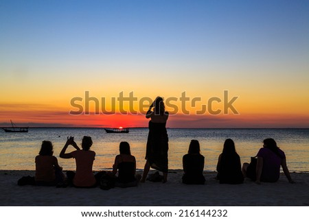 Women sitting on the beach watching the sunset over the ocean - stock photo