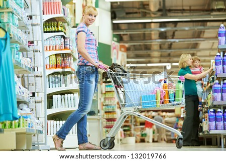 women smiling with shopping cart at supermarket shop mall store - stock photo