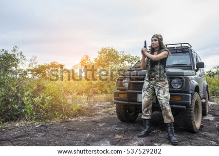 Women soldiers standing in front of car with pistol Get ready to fight on the rocks mountain.
