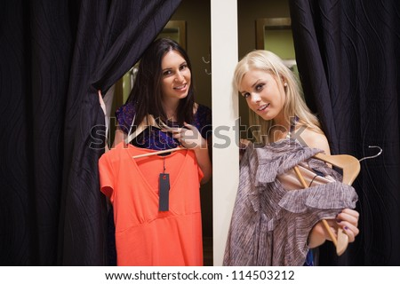 Women stadning in the changing room holding up clothes - stock photo