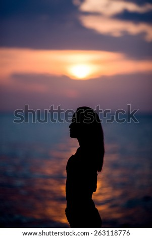 Women stand on beach is silhouette. Time is sunrise and cool. - stock photo