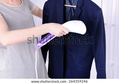 Women steaming shirt in room