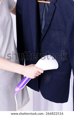 Women steaming shirt in room - stock photo