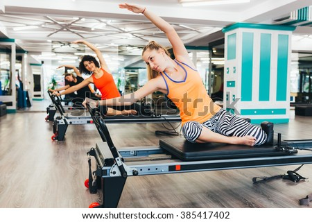 Women stretching on reformer beds  - stock photo