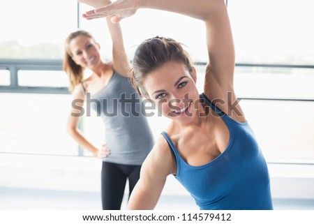 Women stretching their arms in the gym - stock photo