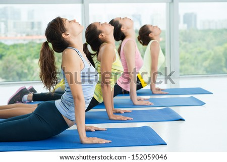 Women stretching their backs in a line  - stock photo
