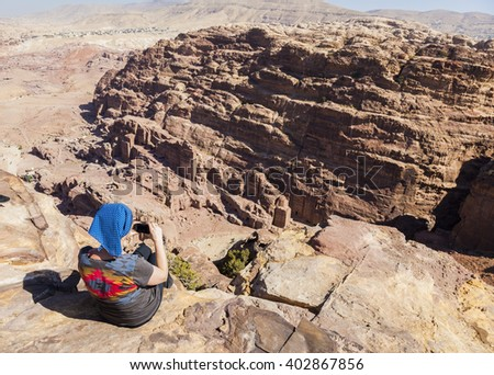 Women takes photo from the cliff edge of High Place of Sacrifice. Petra. Jordan.  - stock photo