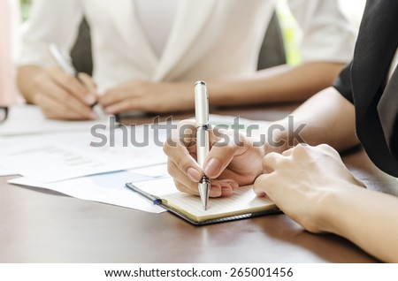 women taking note in a meeting - stock photo
