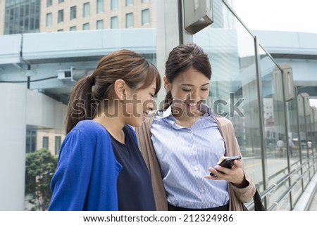 Women talk while watching the smart phone - stock photo