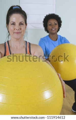 Women using exercise balls in fitness class - stock photo