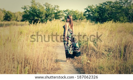 Women walk in a high grass from back in dress - stock photo